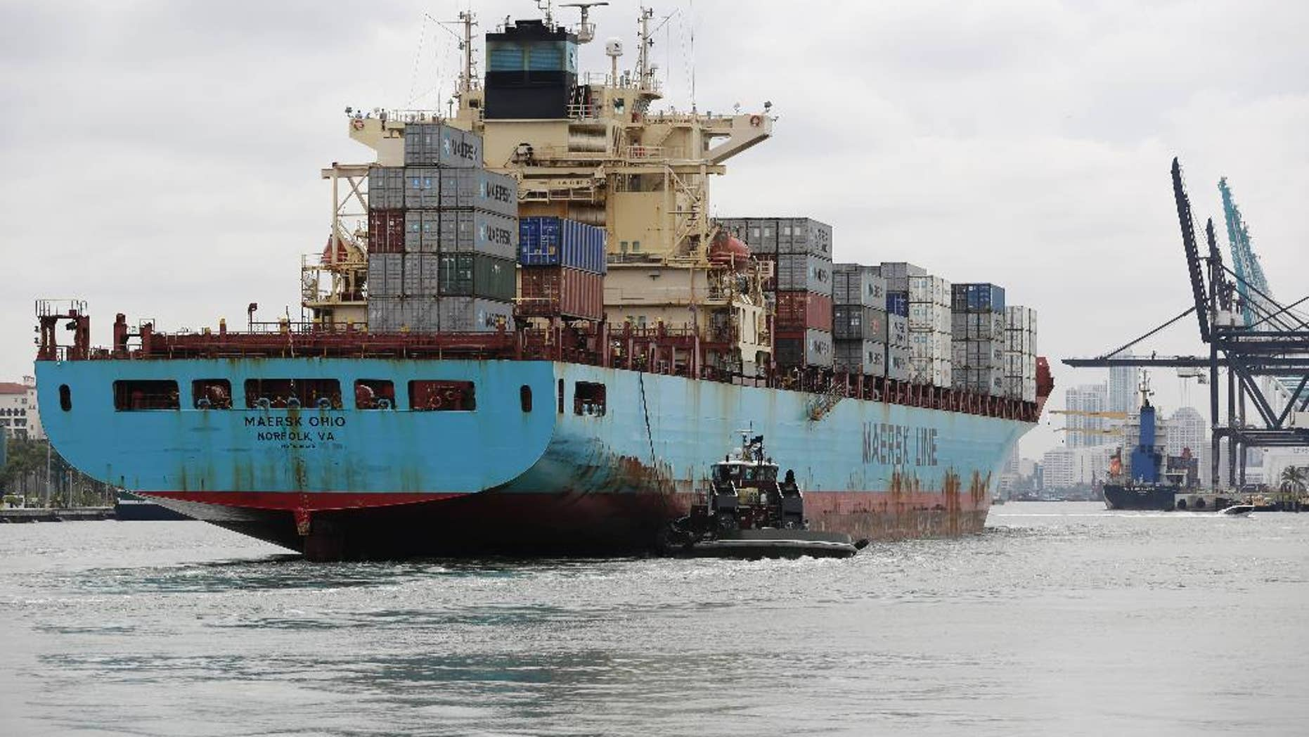 In this Friday, May 16, 2014 photo, a Maersk Line vessel is guided by a tugboat as it heads into the Port of Miami off of Miami Beach, Fla.  The Commerce Department reports on the U.S. current account trade deficit for the April-June quarter on Wednesday, Sept. 17, 2014. (AP Photo/Lynne Sladky)