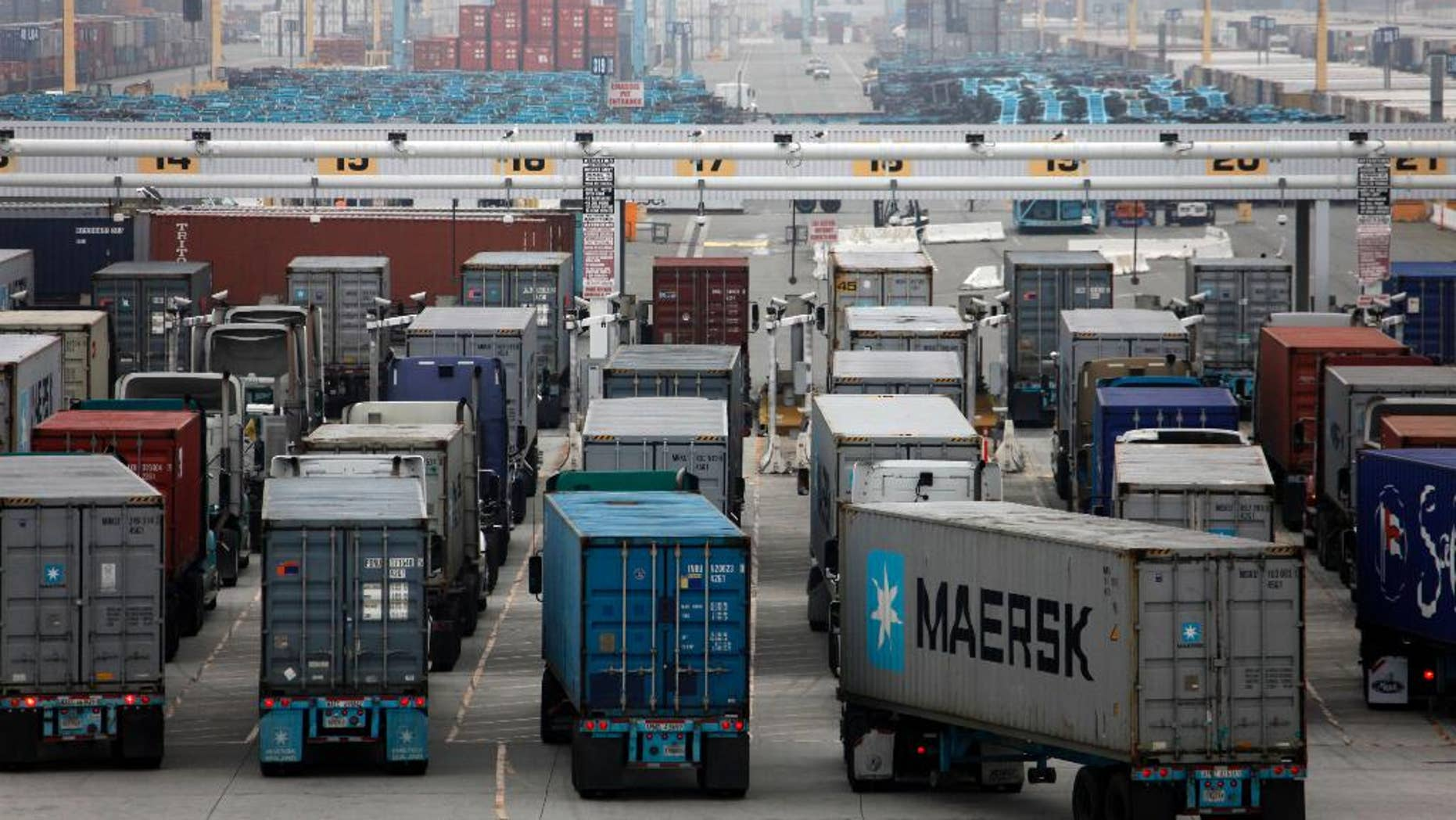 FILE - This Dec. 5, 2014, file photo, shows trucks lined up at the Port of Los Angeles in Los Angeles. The Commerce Department reports on the U.S. current account trade deficit for the October-December quarter on Thursday, March 19, 2015. (AP Photo/Nick Ut, File)