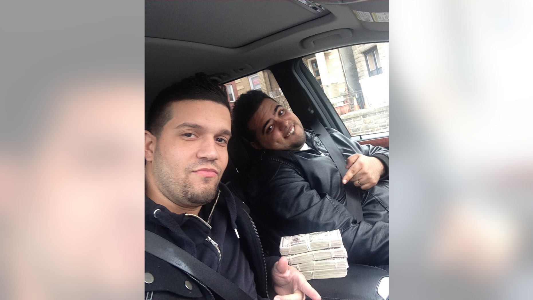 May 9, 2013: In this undated photo provided by the United States Attorneys Office for the Southern District of New York, Elvis Rafael Rodriguez, left, and Emir Yasser Yeje, pose with bundles of cash allegedly stolen using bogus magnetic swipe cards at cash machines throughout New York.
