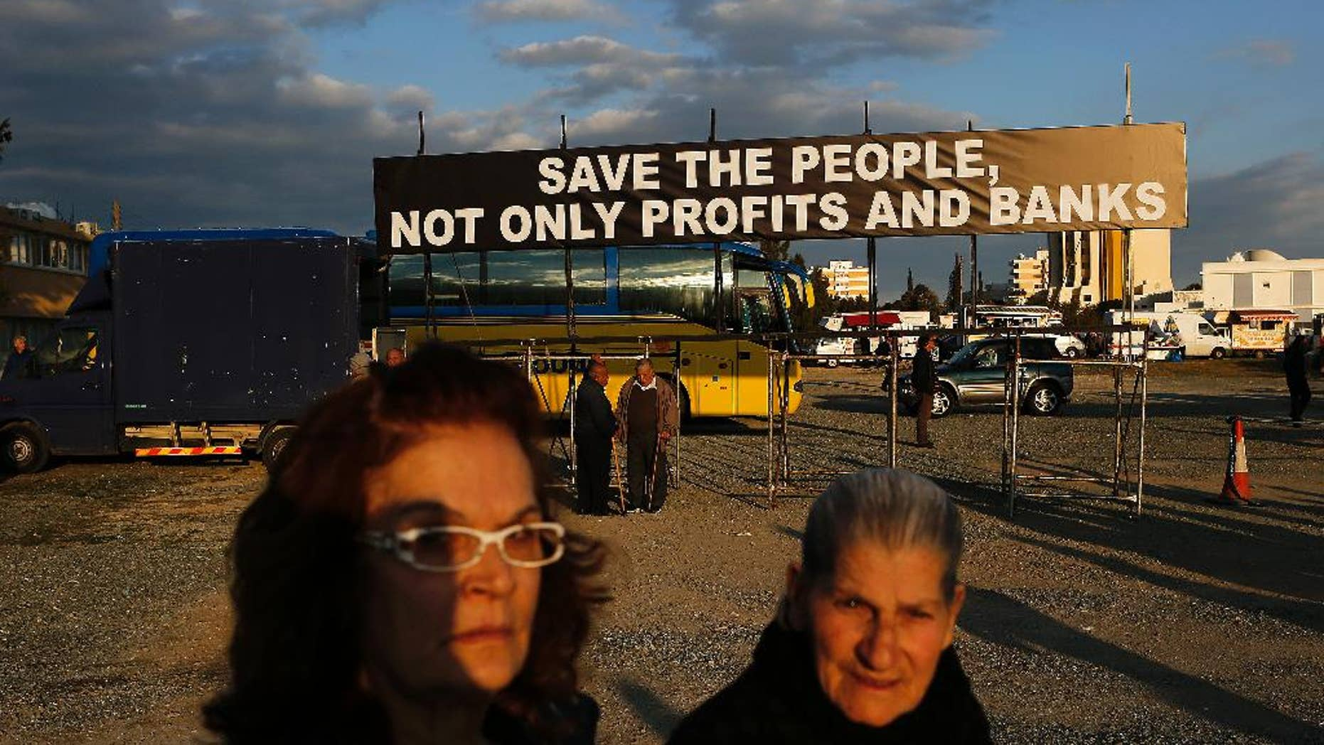 Two protestors walk in front of a banner during an anti austerity demonstration outside a European Central Bank Governing Council meeting at the conference center in capital Nicosia, Cyprus, Wednesday, March 4, 2015. Several thousand demonstrators in Cyprus called for an end to austerity policies they say has driven many in the bailed-out country to poverty. (AP Photo/Petros Karadjias)