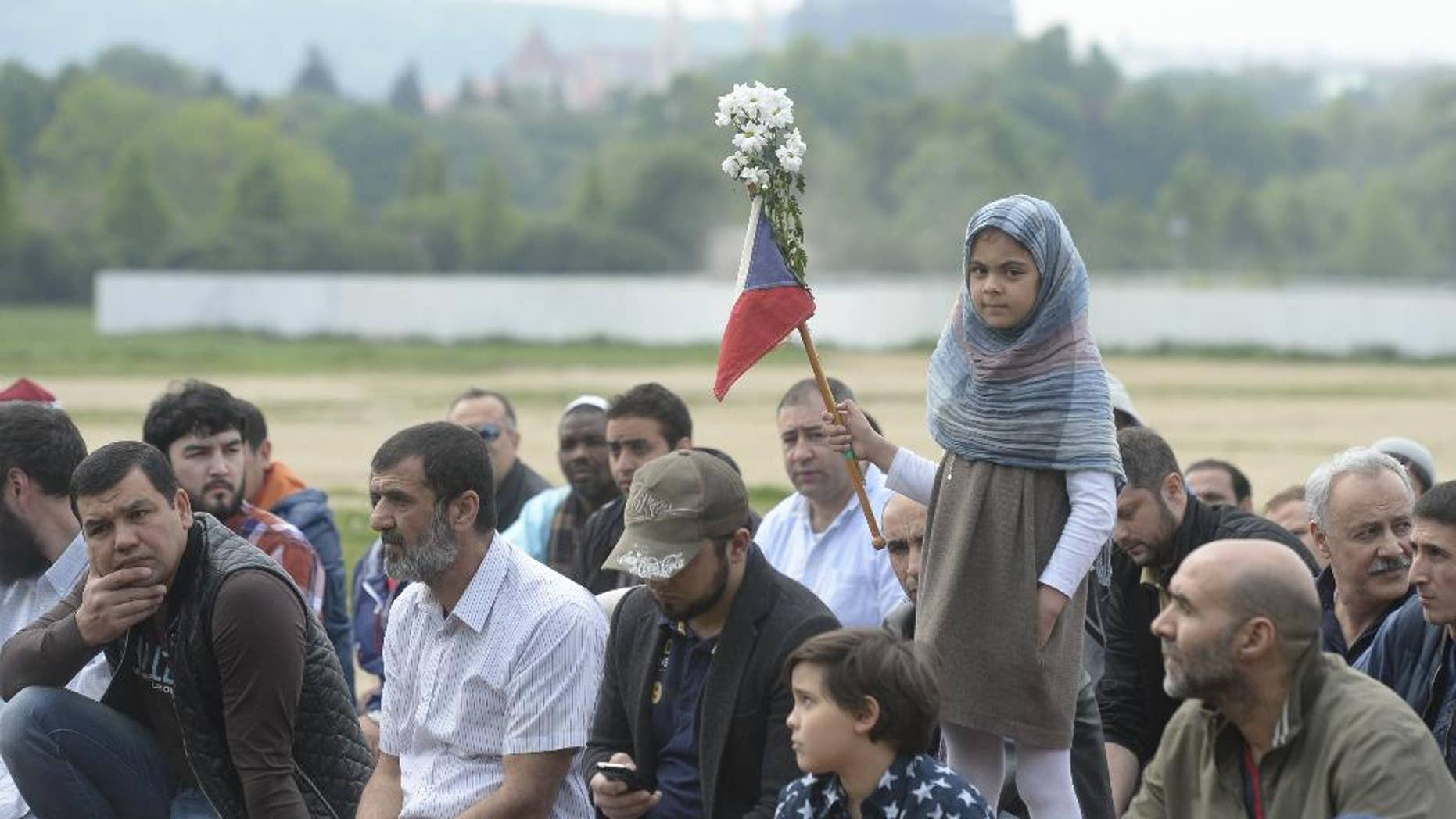 """Muslims living in the Czech Republic pray in front a headquarters of the Ministry of Interior to protest against a police raid in an Islamic center in the Czech capital last week in Prague, on Friday, May 2, 2014. Czech churches have sided with local Muslims who have complained about police raids in Islamic centers during prayers. The raids took place last Friday in Prague as police arrested a 55-year-old Czech who was charged with racism for publishing an Islamic book that police alleged spreads racism, anti-Semitism, xenophobia and violence against """"inferior races.""""  (AP Photo/CTK, Michal Krumphanzl) SLOVAKIA OUT"""
