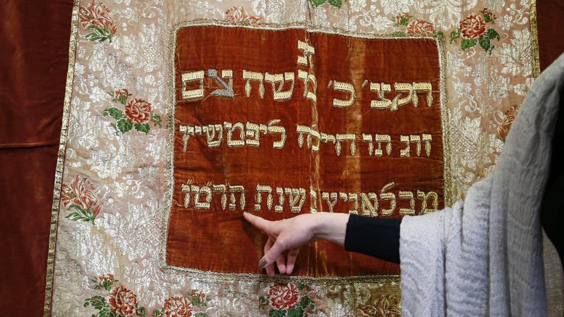 Visual arts curator of Jewish Museum in Prague Michaela Sidenberg points to details on a synagogue textile in Prague, Czech Republic, Wednesday, March 26, 2014. This textile stolen by the Nazis during the World War II has returned to the Czech Republic after it has been found in the United States. It is for the first time that a ritual Jewish property that was stolen during the Holocaust has been traced abroad and returned home. (AP Photo/Petr David Josek)