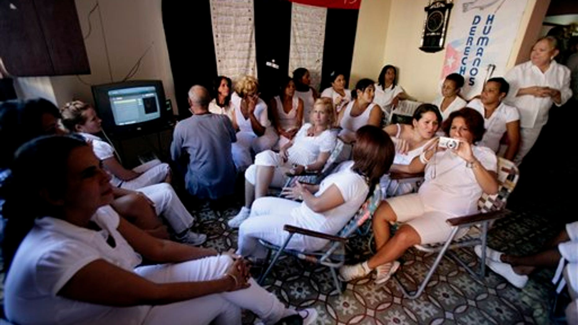 Members of Cuban dissident group Ladies in White gather in a home to commemorate the anniversary of the 2003 government crackdown on dissidents in Havana, Cuba, Friday March 18, 2011. Some 75 activists, intellectuals and social commentators were arrested in the 2003 sweep and sentenced to long jail terms. The government agreed last year to free all that remained in prison, and two of those arrested in the crackdown are still being held. (AP Photo/Javier Galeano)
