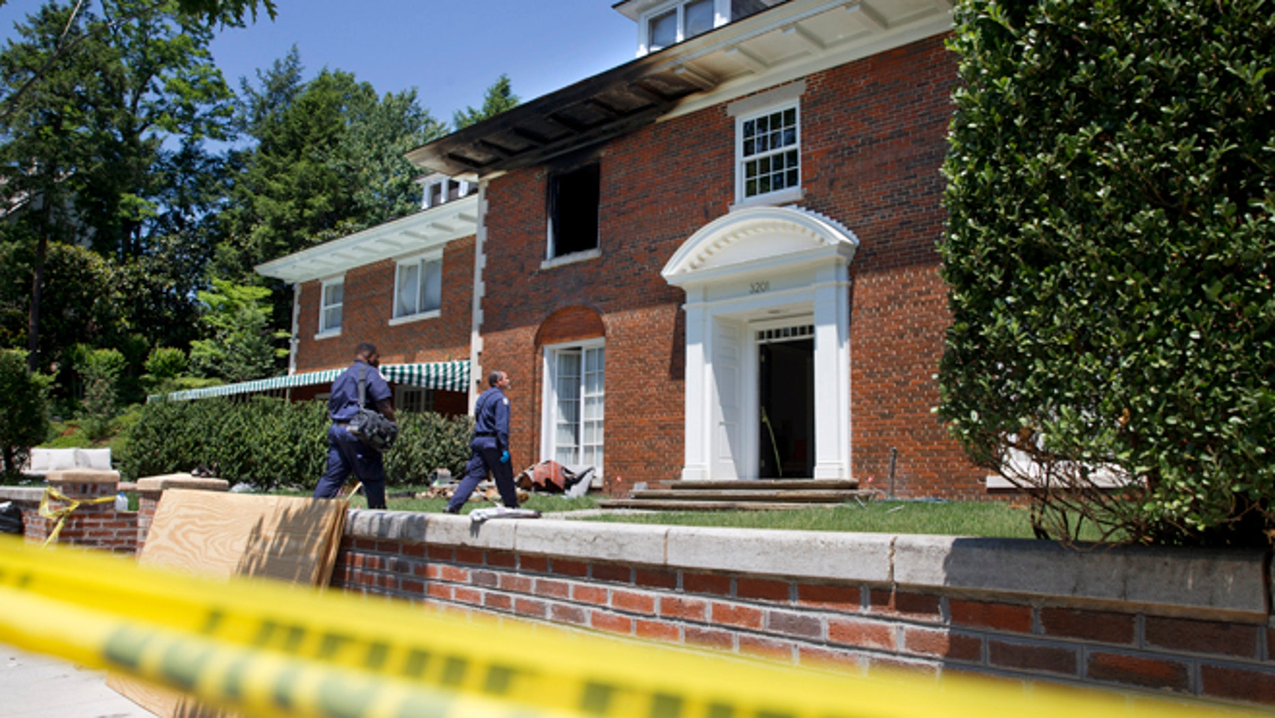 Police continue working at a fire-damaged multimillion-dollar home in northwest Washington home, Friday May 22, 2015, where 46-year-old Savvas Savopoulos, his 47-year-old wife, Amy Savopoulos, the couple's 10-year-old son Philip, and housekeeper Veralicia Figueroa were found dead May 14. U.S. marshals and police arrested a dangerous ex-convict and took his five companions into custody, safely ending a multistate manhunt in the slayings of a wealthy Washington family and their housekeeper. The fugitive task force tracked Daron Dylon Wint to New York and back before they caught up with him late Thursday (AP Photo/Jacquelyn Martin)