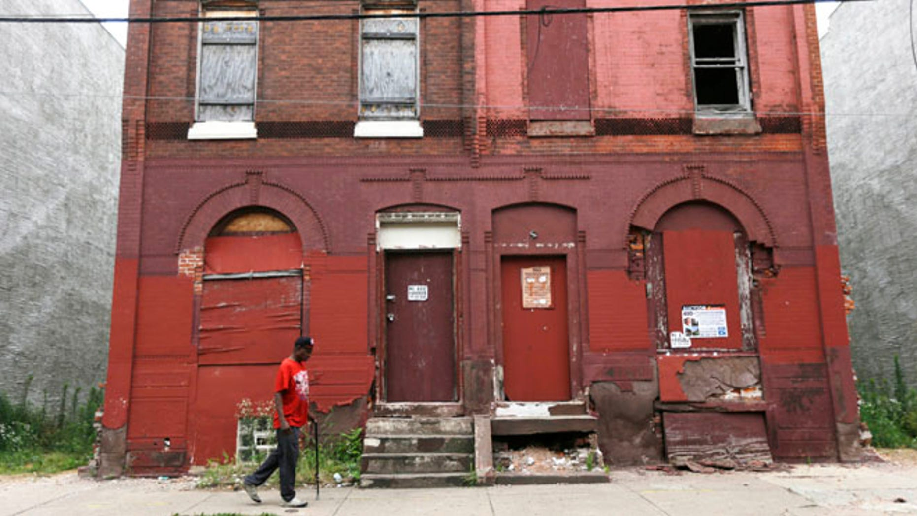 FILE - In this July 11, 2013 file photo a man walks through a blighted neighborhood in Philadelphia. Democrats are set to begin their convention Monday, July 25, 2016, in a city that symbolizes both the nation's promise and its shortcomings. (AP Photo/Matt Rourke, File)