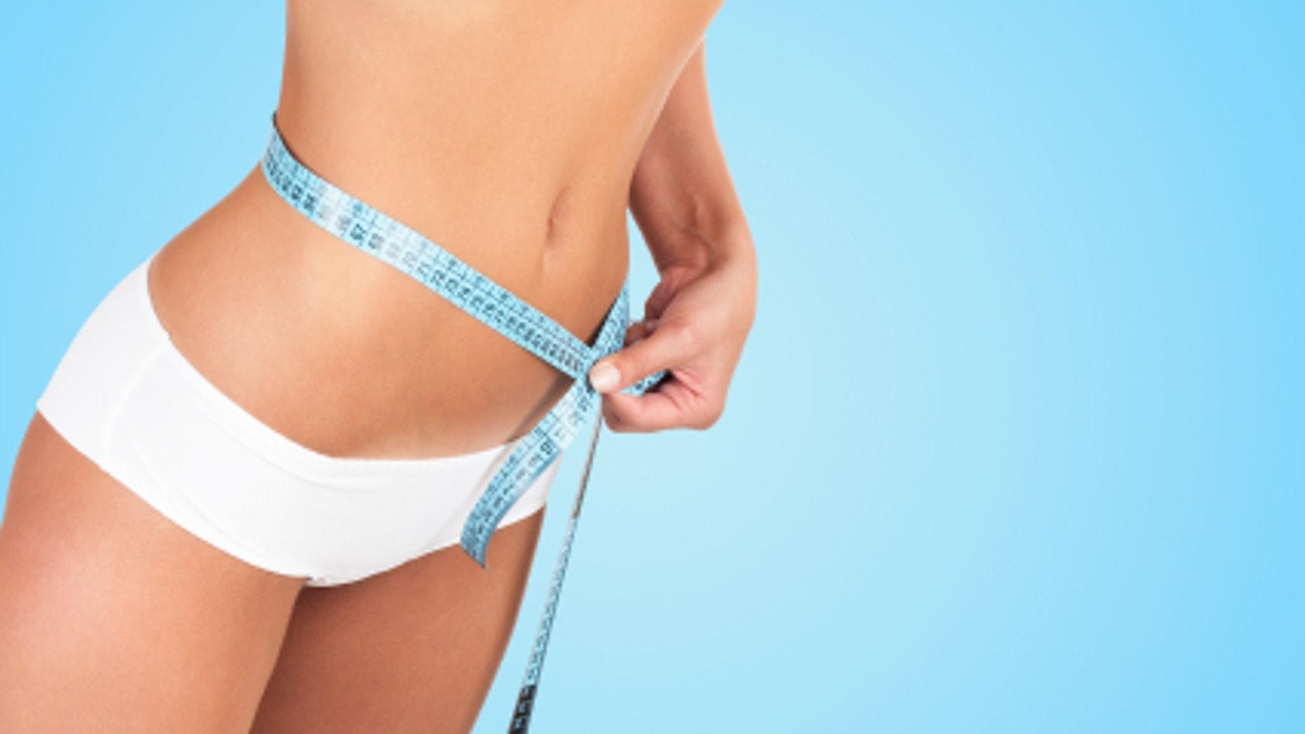 Beautiful woman measuring her waist - high key shot in studio