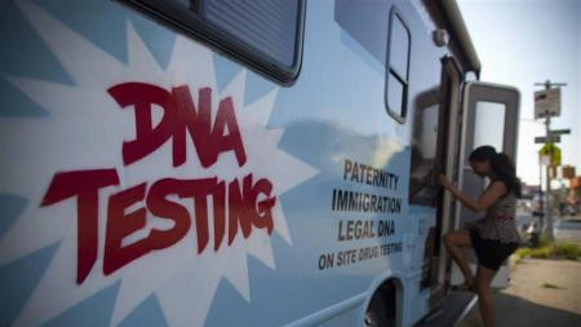 """A woman enters the """"Who's Your Daddy?"""" DNA testing van in the Bronx neighborhood of New York."""