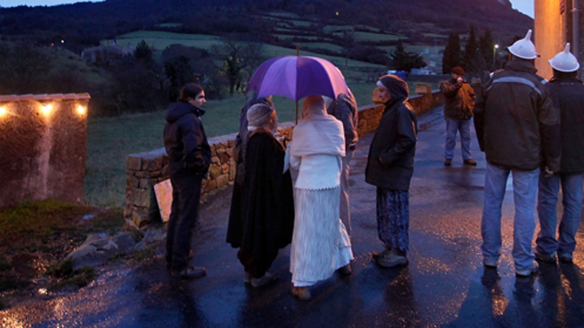People gather at dusk in Bugarath, a small village in the foothills of the Pyrenees on December 20, 2012 in Bugarach, France.