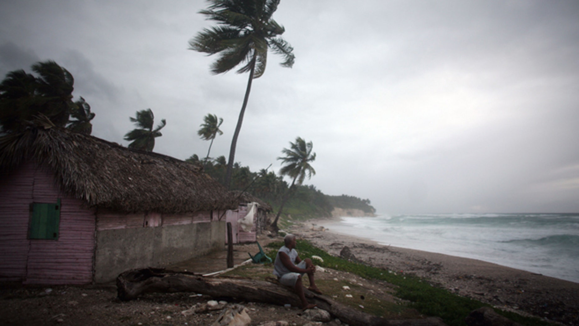 A man look out at the beach as Tropical Storm Isaac approaches in Barahona, Dominican Republic, Friday, Aug. 24, 2012.  (AP Photo/Ricardo Arduengo)