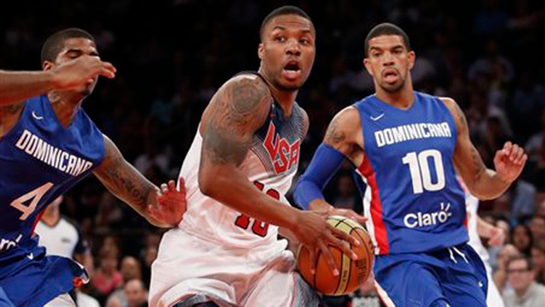 Dominican Republic guards Edgar Sosa (4) and James Feldeine (10) defend as United States guard Kyrie Irving (10) looks to pass while heading toward the basket in the first half of an exhibition basketball game at Madison Square Garden in New York, Wednesday, Aug. 20, 2014. (AP Photo/Kathy Willens)