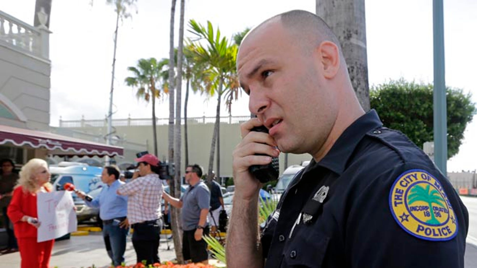 City of Miami police officer R. Delgado covers his badge with a black band as he honors the death of police officers in Dallas, Friday, July 8, 2016, at a Republican presidential candidate Donald Trump campaign stop. Trump has called off his two Friday campaign events in Miami in the wake of deadly sniper killings of Dallas police officers. (AP Photo/Alan Diaz)