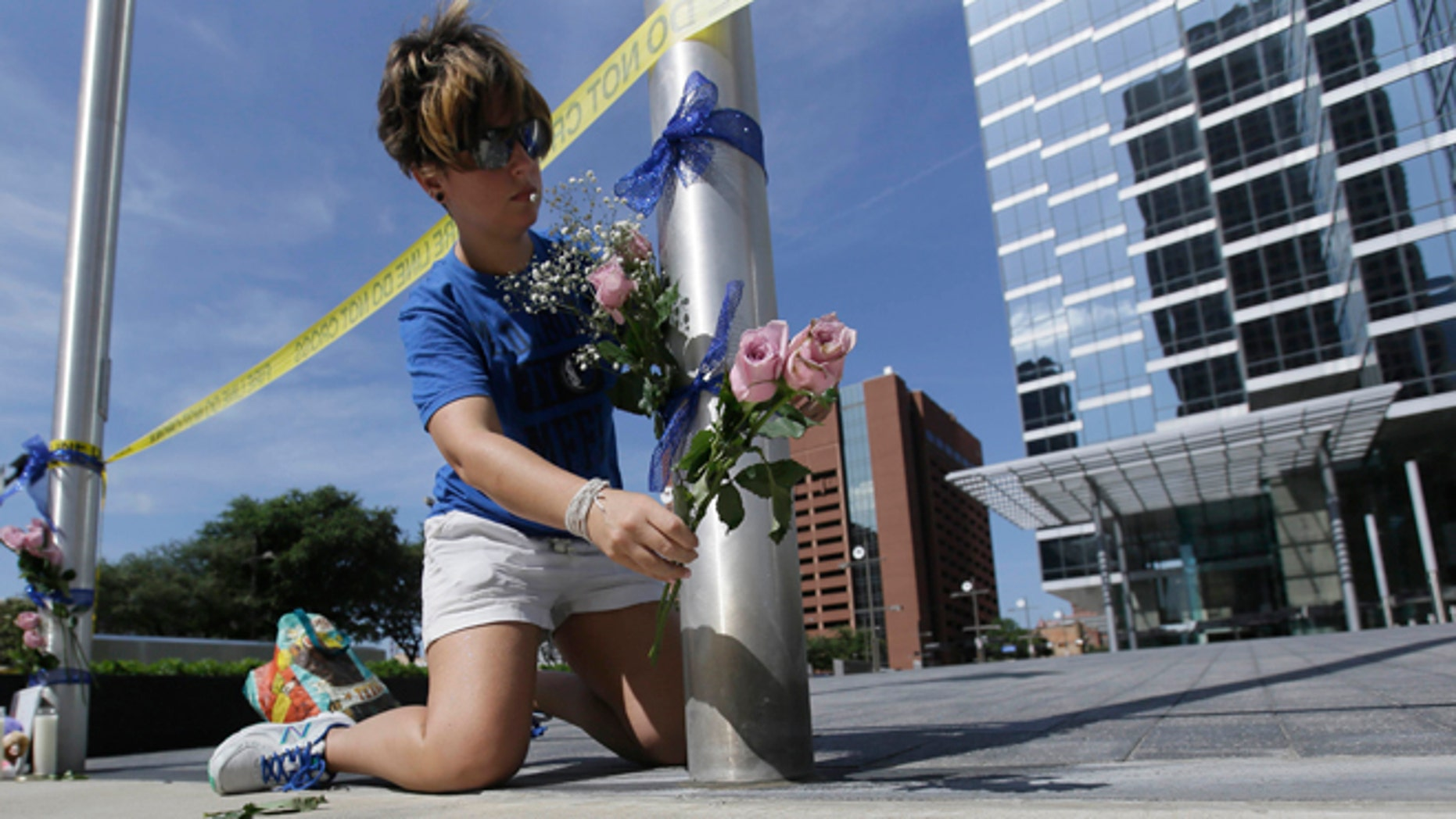 Noelle Hendrix places flowers near the scene of a shooting in downtown Dallas, Friday, July 8, 2016. Snipers opened fire on police officers in the heart of Dallas during protests over two recent fatal police shootings of black men. (AP Photo/LM Otero)