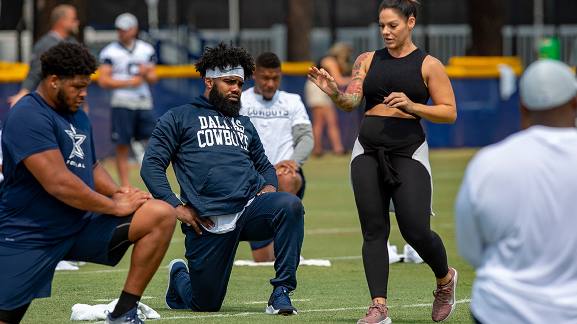 FILE - In this July 28, 2018, file photo, Dallas Cowboys offensive tackle La'el Collins, left and running back Ezekiel Elliott, center, listen to yoga instructor Stacey Hickman, right, as the team does some flexibility exercises at NFL football training camp in Oxnard, Calif. (AP Photo/Gus Ruelas, File)