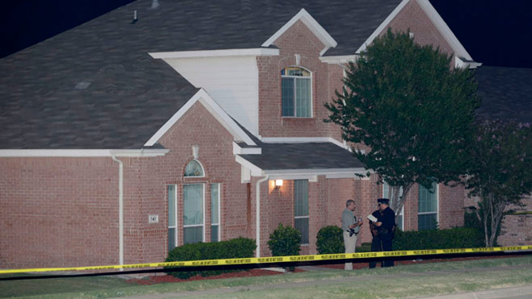 Aug. 8: Law enforcement officers confer outside the house of a fatal shooting in DeSoto, Texas.