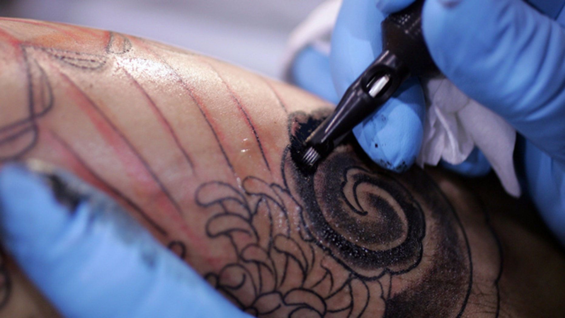 FILE - This Jsn. 6, 2006, file photo shows a tattoo artist from Los Angels during the Body Art Expo at the Los Angeles county fairgrounds in Pomona, Calif. (AP Photo/Chris Carlson, File)