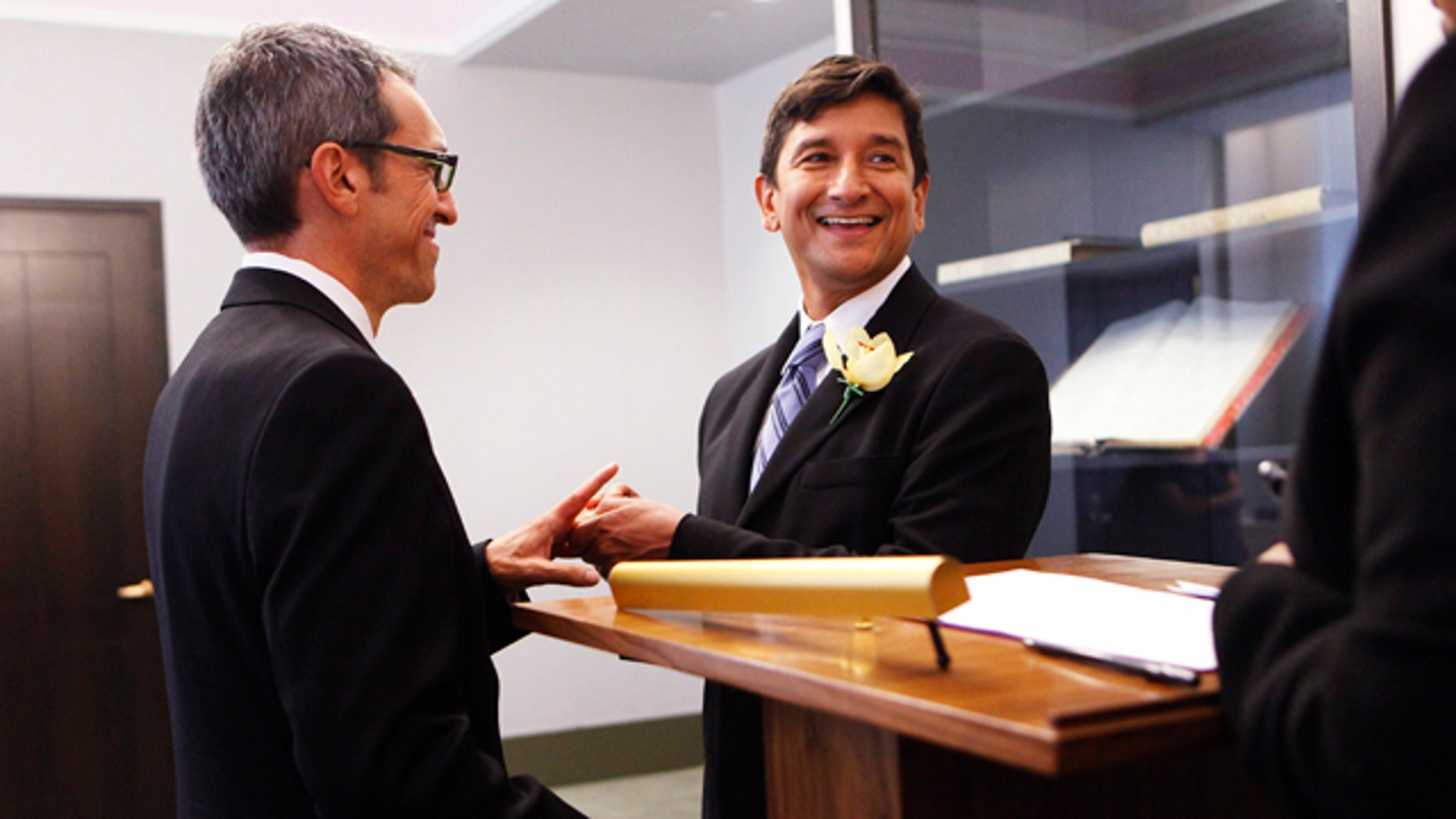 Same-sex couple Daniel Hernandez, 53, right, and Nevin Cohen, 48, exchange vows at the City Clerk's Office in New York on July 24, 2011, a month after Gov. Cuomo signed a state law legalizing gay marriage. (AP Photo/Shannon Stapleton, Pool)