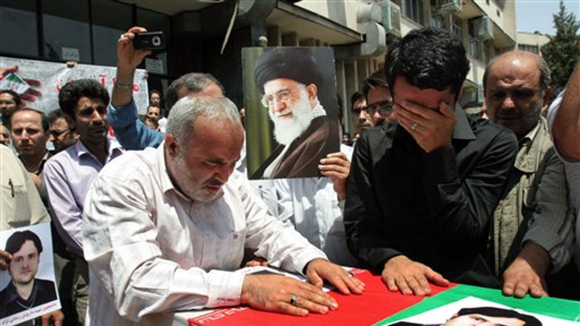 July 24: Relatives and friends mourn over the coffin of Darioush Rezaeinejad, shown in the picture on the coffin, in a funeral ceremony in Tehran, Iran, who was killed in a deadly shooting on Saturday.