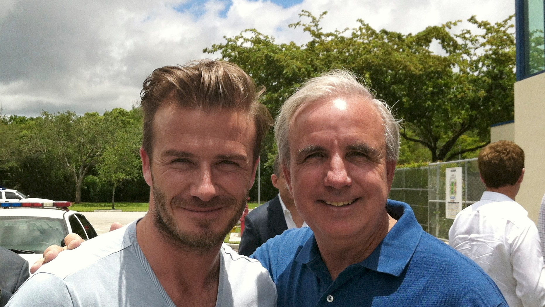 In this undated photo released by Miami-Dade County, former soccer star David Beckham poses for a photo with Miami-Dade County Mayor Carlos Gimenez, in Miami. Beckham may be setting his sights on a new sports venture: A professional soccer team in Miami. The newly retired Beckham toured Sun Life and Florida International University stadiums and met with Miami-Dade County Mayor Carlos Gimenez on Saturday. (AP Photo/Miami-Dade County)