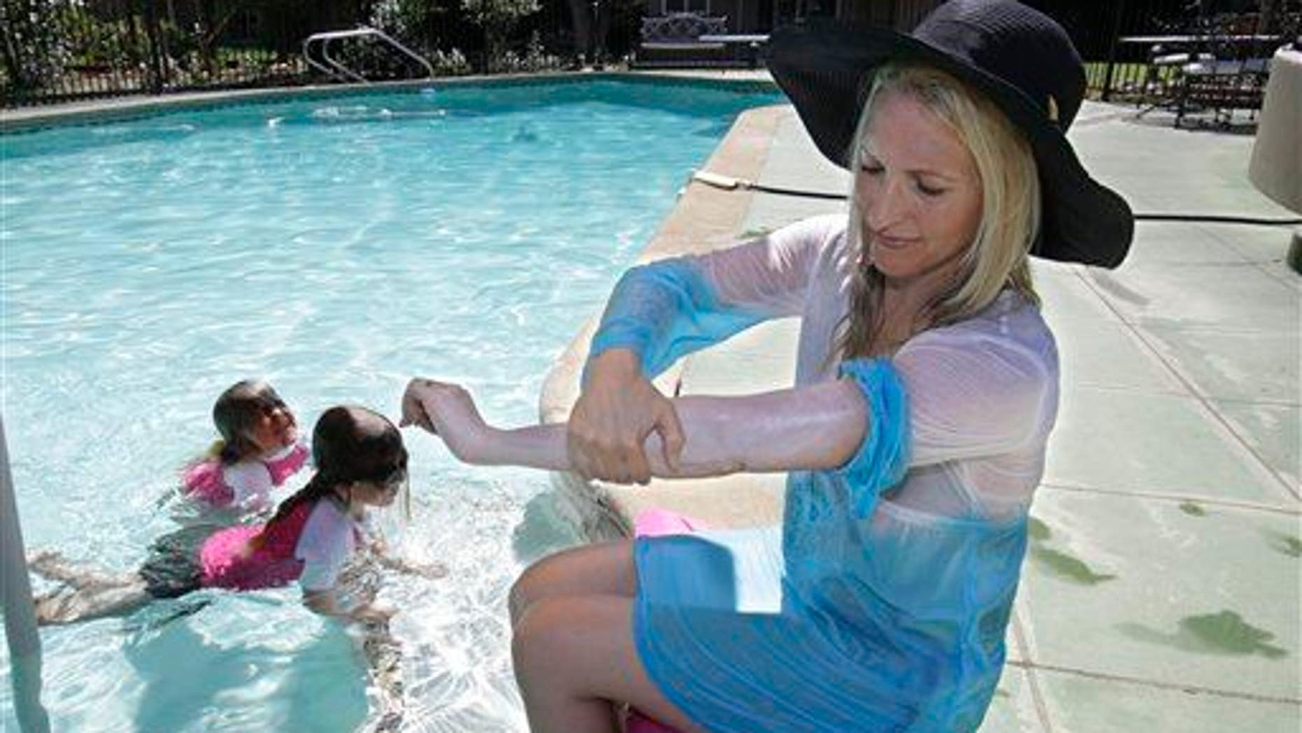 In this Wednesday, June, 22, 2011, photo,  a woman who was diagnosed with malignant melanoma at 35 puts on sun screen while poolside with her daughters at their home in Carmichael, Calif.