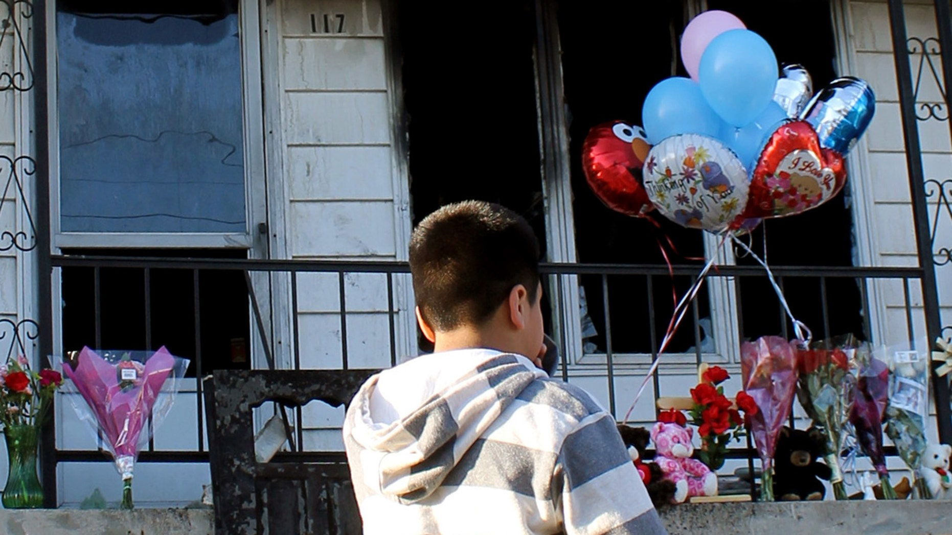 Javier Alcala stands in front of the home of his friends, Christian Sanchez and Damian Lopez, who were victims of a deadly fire that occurred on Tuesday, March 27, 2012, in Shenandoah, Pa. The fire destroyed five row homes, killing a woman and three children in one house while a fourth child managed to escape out a second floor window as the flames closed in, fire officials said. The Schuylkill County coroner's office identified the victims as Tiffany Sanchez, 28; her 10-year-old son Christian; and her two nephews, 10-year-old Damien Lopez and 7-month-old Aziah Hernandez. (AP Photo/Hazleton Standard-Speaker, Jamie Pesotine)