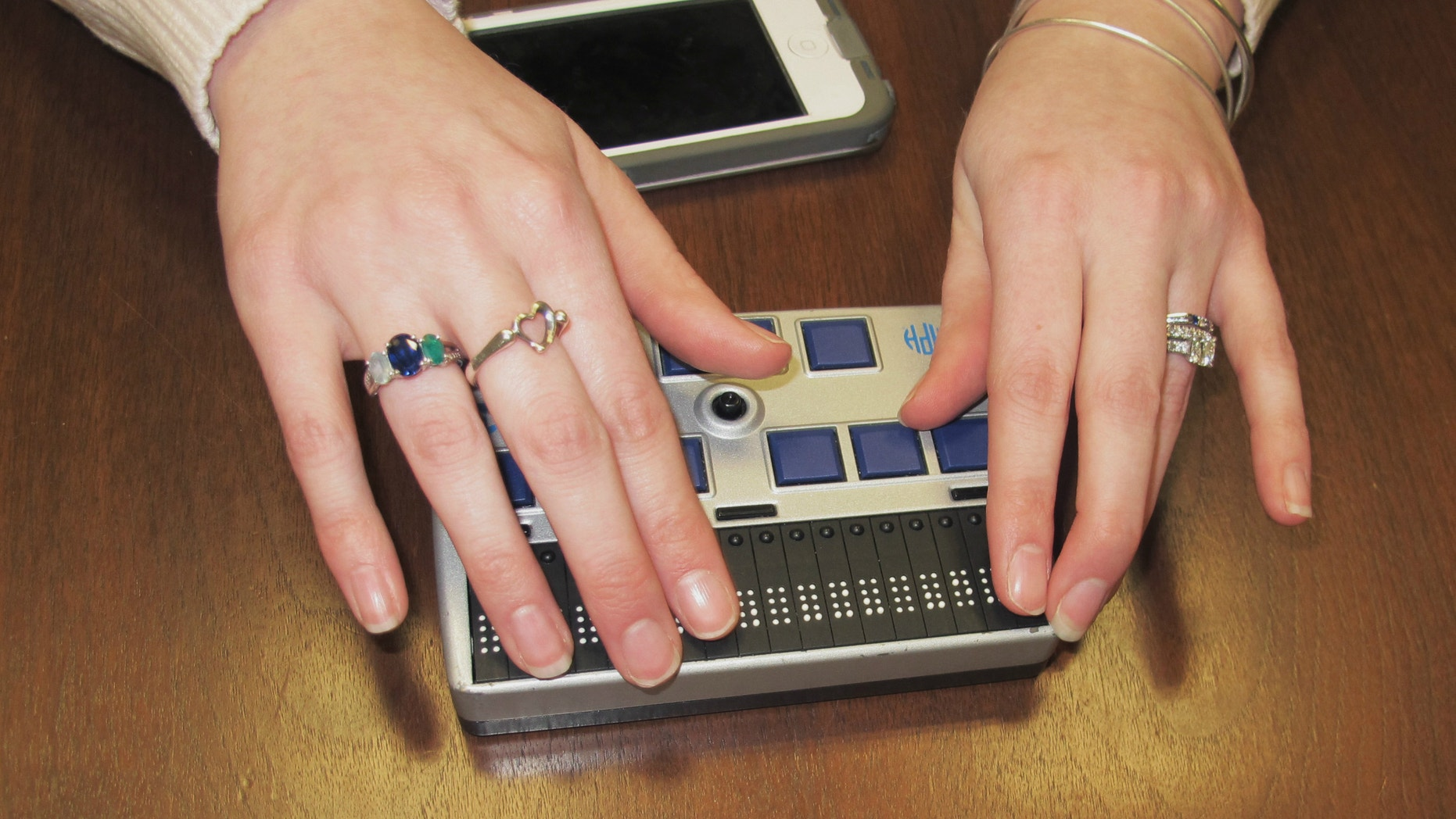 Megan Dausch, an instructor at the Helen Keller National Center, demonstrates the use of a Braille reader that helps blind clients access the Internet.