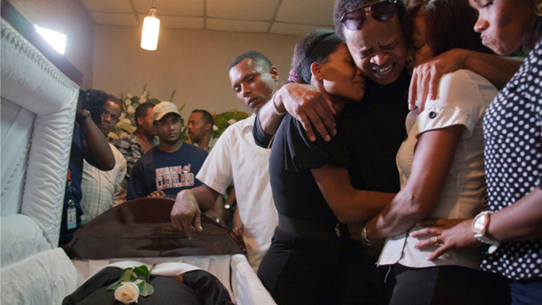 Kansas City Royals player Edinson Volquez, third from Right, embraces his sister Wendy Volquez, left, and mother Ana Ramirez as they stand next to the body of his father during his wake at a funeral home in Santo Domingo, Dominican Republic, Wednesday, Oct. 28, 2015.  (AP Photo/Tatiana Fernandez)