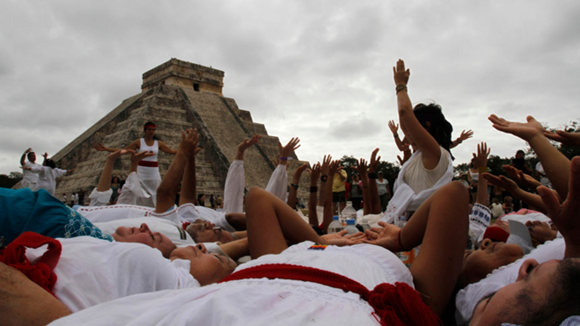 People participate in a ritual in fron of Kukulkan temple in Chichen Itza, Mexico, Friday, Dec. 21, 2012. At the ruins of the ancient Mayan city of Chichen Itza, thousands chanted, danced and otherwise frolicked around ceremonial fires and pyramids to mark the conclusion of a vast, 5,125-year cycle in the Mayan calendar. (AP Photo/Israel Leal)