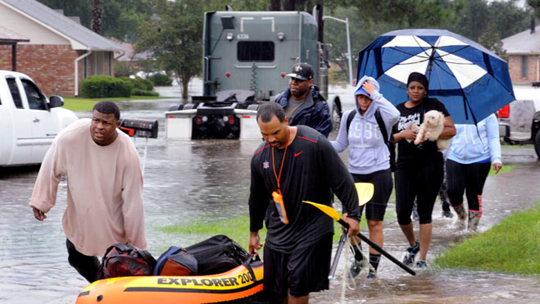 Residents use a raft to evacuate as others walk out of their neighbor Saturday, Aug. 13, 2016, in Baton Rouge, La.
