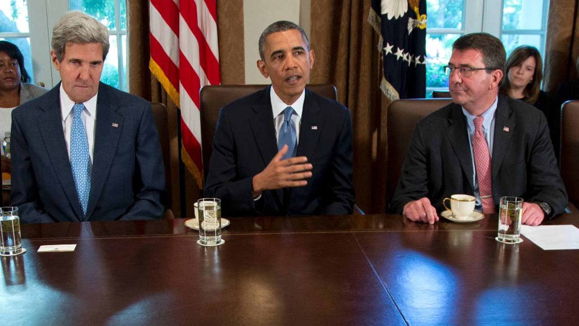 FILE - In this Sept. 30, 2013 file photo, then-Deputy Defense Secretary Ashton Carter, right, listens a President Barack Obama speaks to members of the media in the Cabinet Room of the White House in Washington. Carter has emerged as President Barack Obama's top candidate to become the next defense secretary, according to administration officials, putting him in line to take over a sprawling department that has had an uneasy relationship with the White House. Secretary of State John Kerry is at left.  (AP Photo/Carolyn Kaster, File)