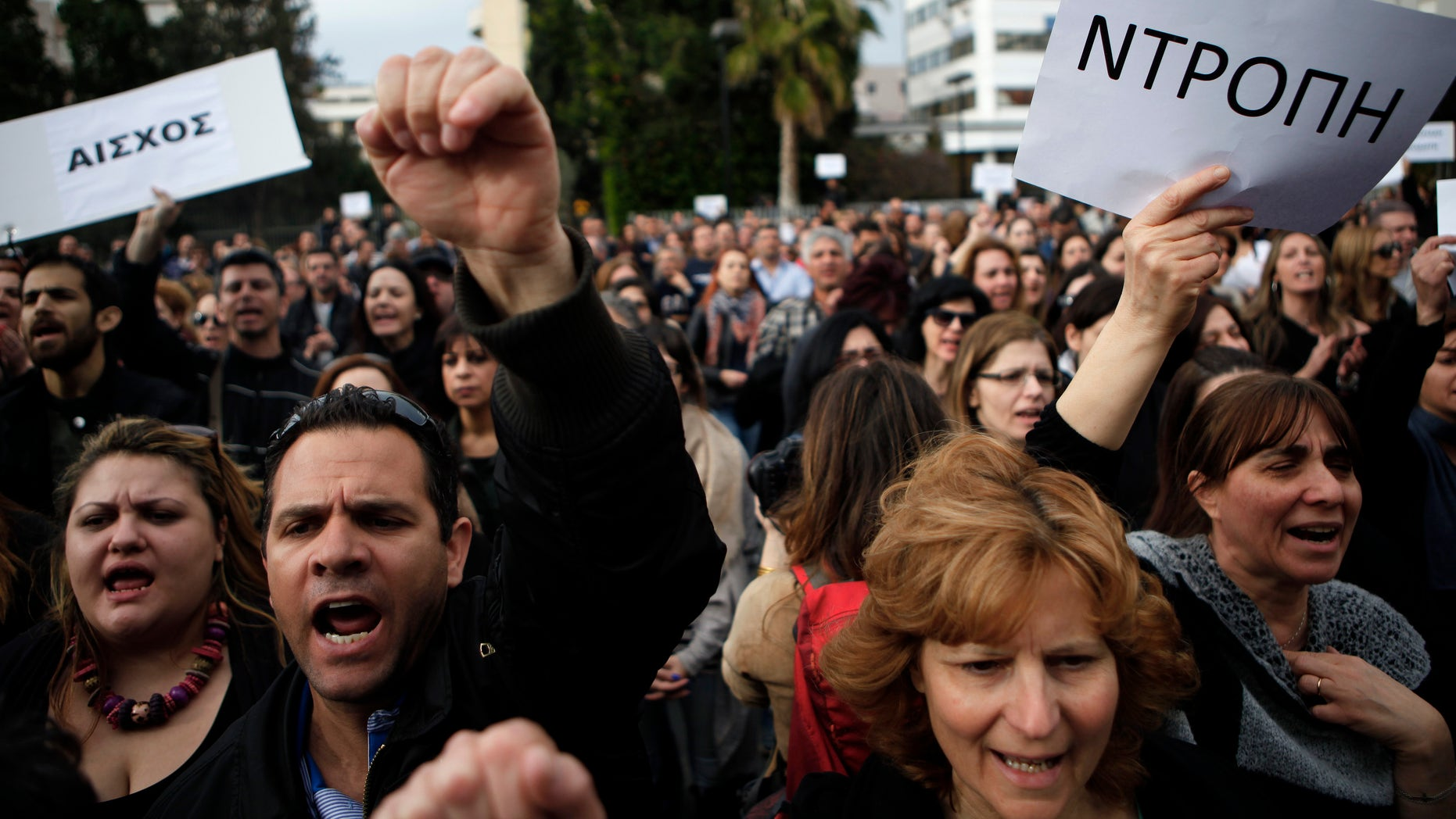 """FILE- In this Tuesday, March 26, 2013 file photo, employees of the Bank of Cyprus shout slogans as they holds banners reading in Greek """"shame"""" during a protest at Cyprus central bank in Nicosia, Cyprus. The moment word broke that Cypriot lawmakers in Parliament had voted down a bailout deal that would have raided everyone's savings to prop up a collapsing banking sector, a huge cheer rose up from hundreds of demonstrators gathered outside that echoed through the building's corridors. Many relished it as a kind of David-against-Goliath moment  a country of barely a million people standing up to the will of Europe's behemoths who wanted it to swallow a very bitter pill to fix its broken-down economy. (AP Photo/Petros Karadjias, File)"""