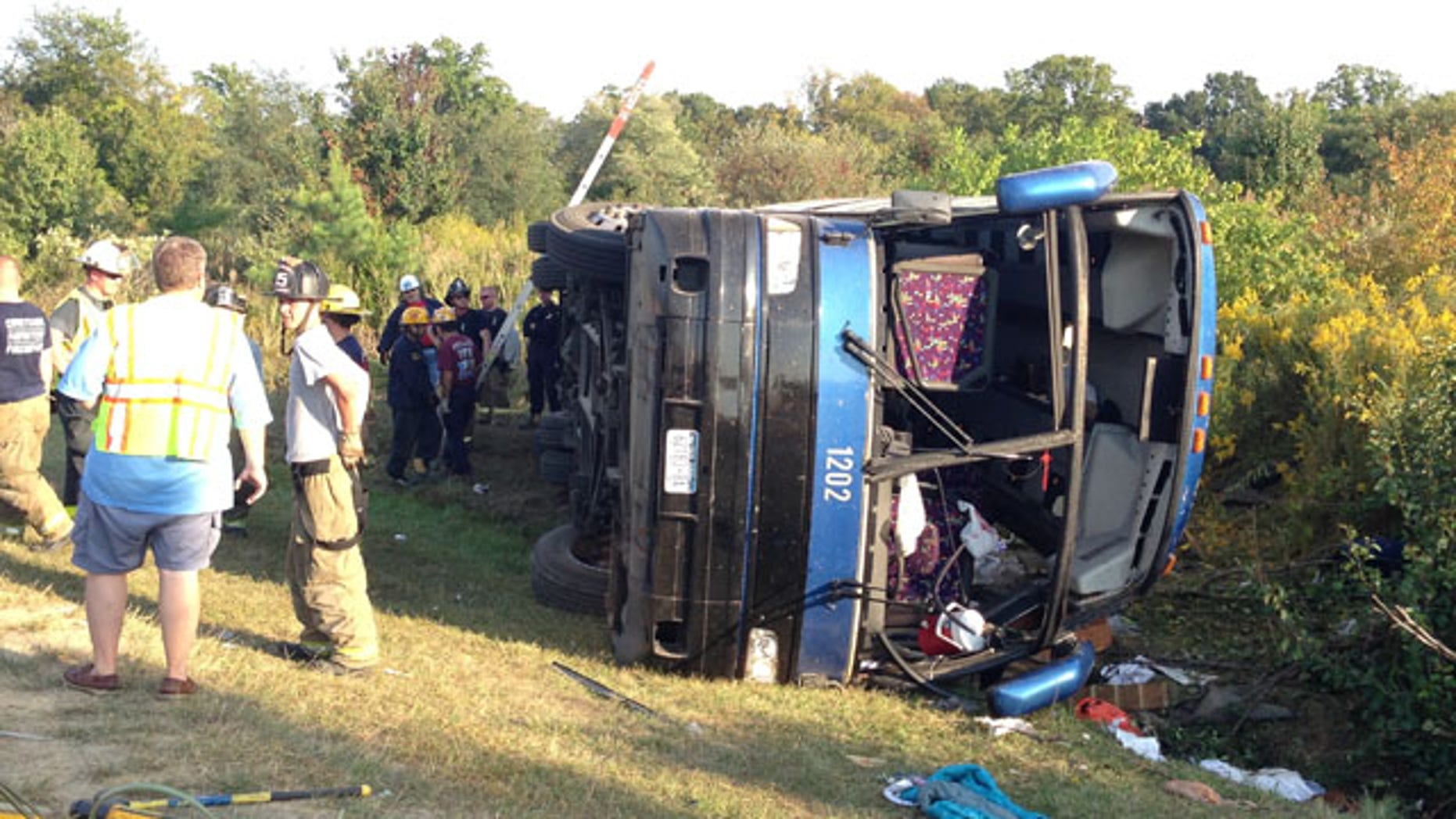 September 21, 2014: Passengers from a tour bus are treated for injuries near the overturned bus at the Tybouts Corner on ramp from southbound Del. 1 to Red Lion Road. (AP Photo/The Wilmington News-Journal, John J. Jankowski)