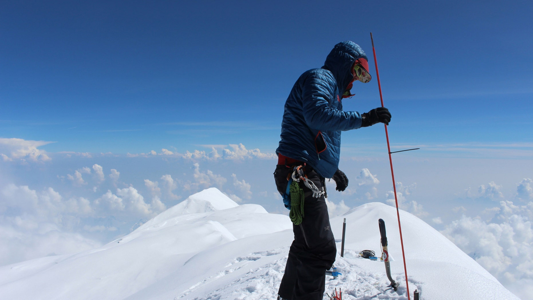 In this June 24, 2015, photo provided by Compass Data/USGS, Blaine Horner of CompassData probes the snow pack at the highest point in North America along with setting up Global Position System equipment for precise summit elevation data on top of Denali in Denali National Park, Ak.