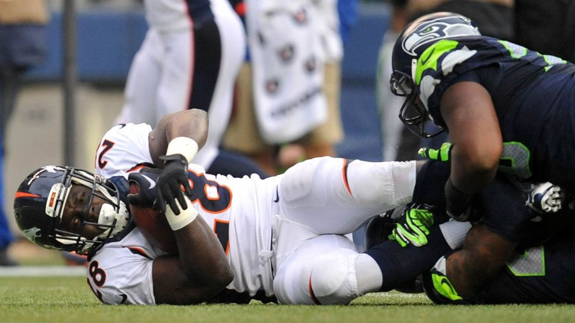 August 14, 2015; Seattle, WA, USA; Denver Broncos running back Montee Ball (28) is brought down by the Seattle Seahawks defense during the first half in a preseason NFL football game at CenturyLink Field. Mandatory Credit: Gary A. Vasquez-USA TODAY Sports