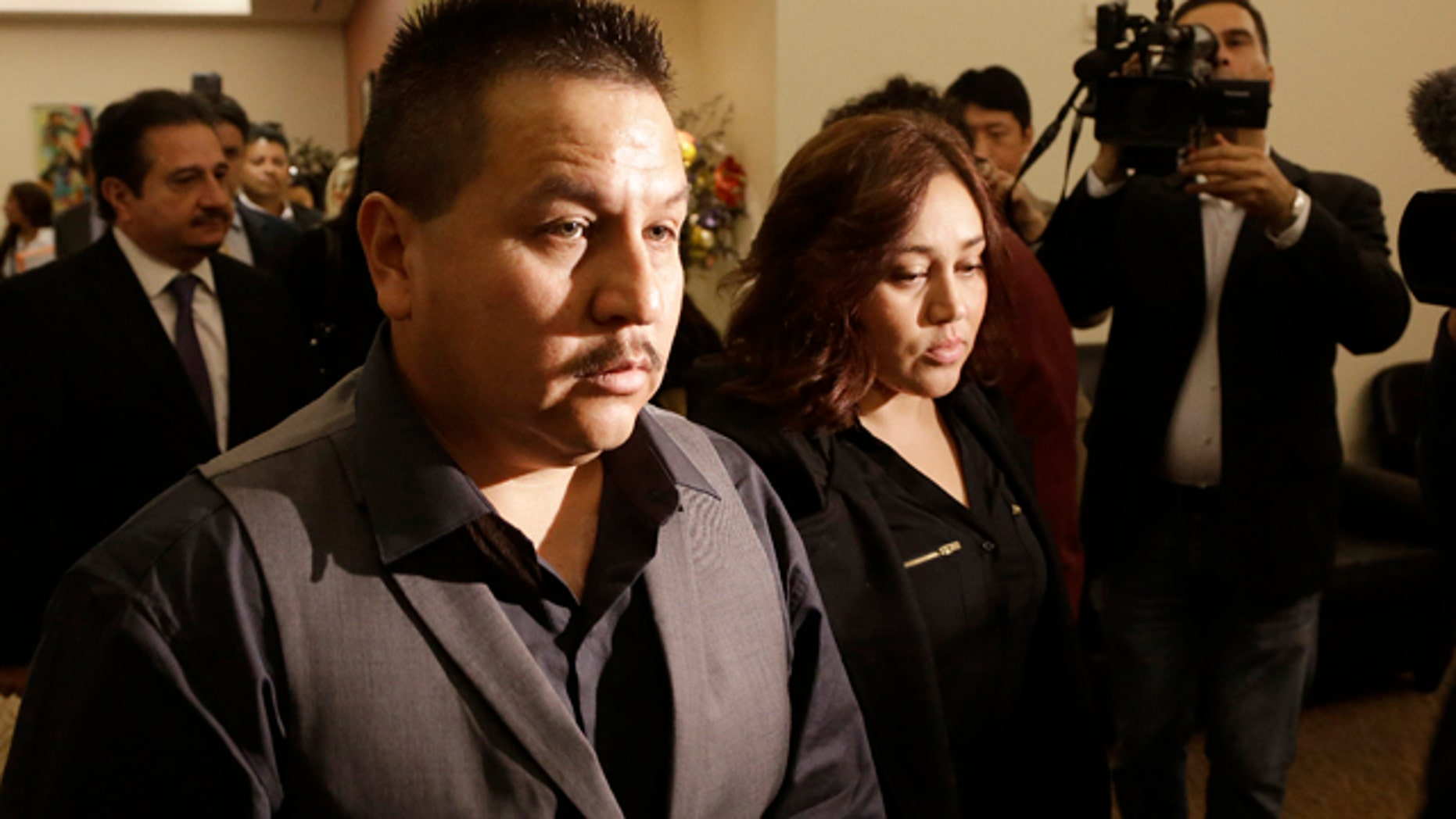 File - This Nov. 4, 2013 file photo shows Rodrigo Lopez, left, and Sujay Cruz, parents of Andy Lopez, as they walk to a news conference in San Francisco. (AP Photo/Jeff Chiu, file)