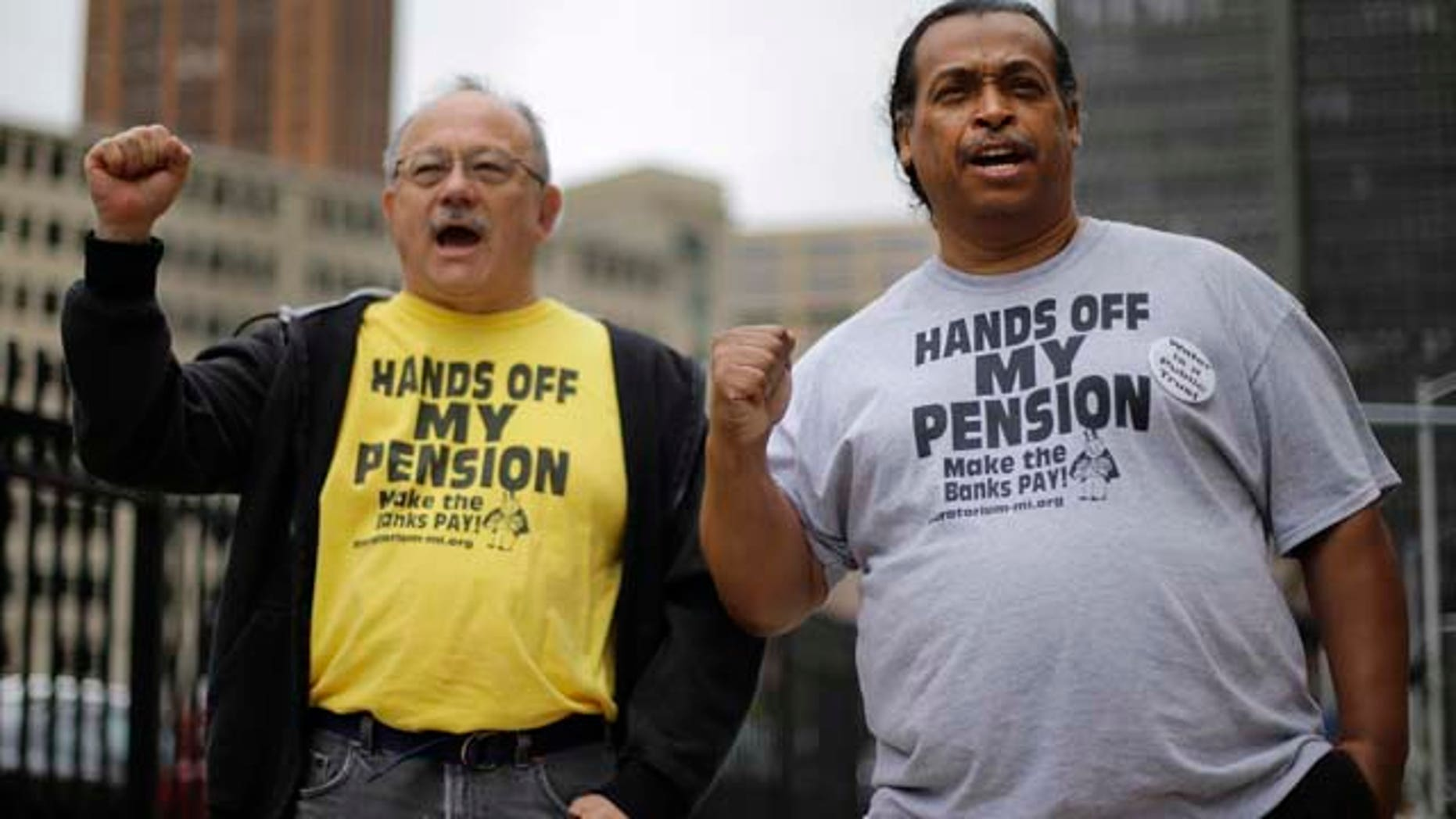 FILE - In a Thursday, July 3, 2014 file photo, Detroit retirees Mike Shane, left, and William Davis protest near the federal courthouse in Detroit. (AP Photo/Paul Sancya, File)