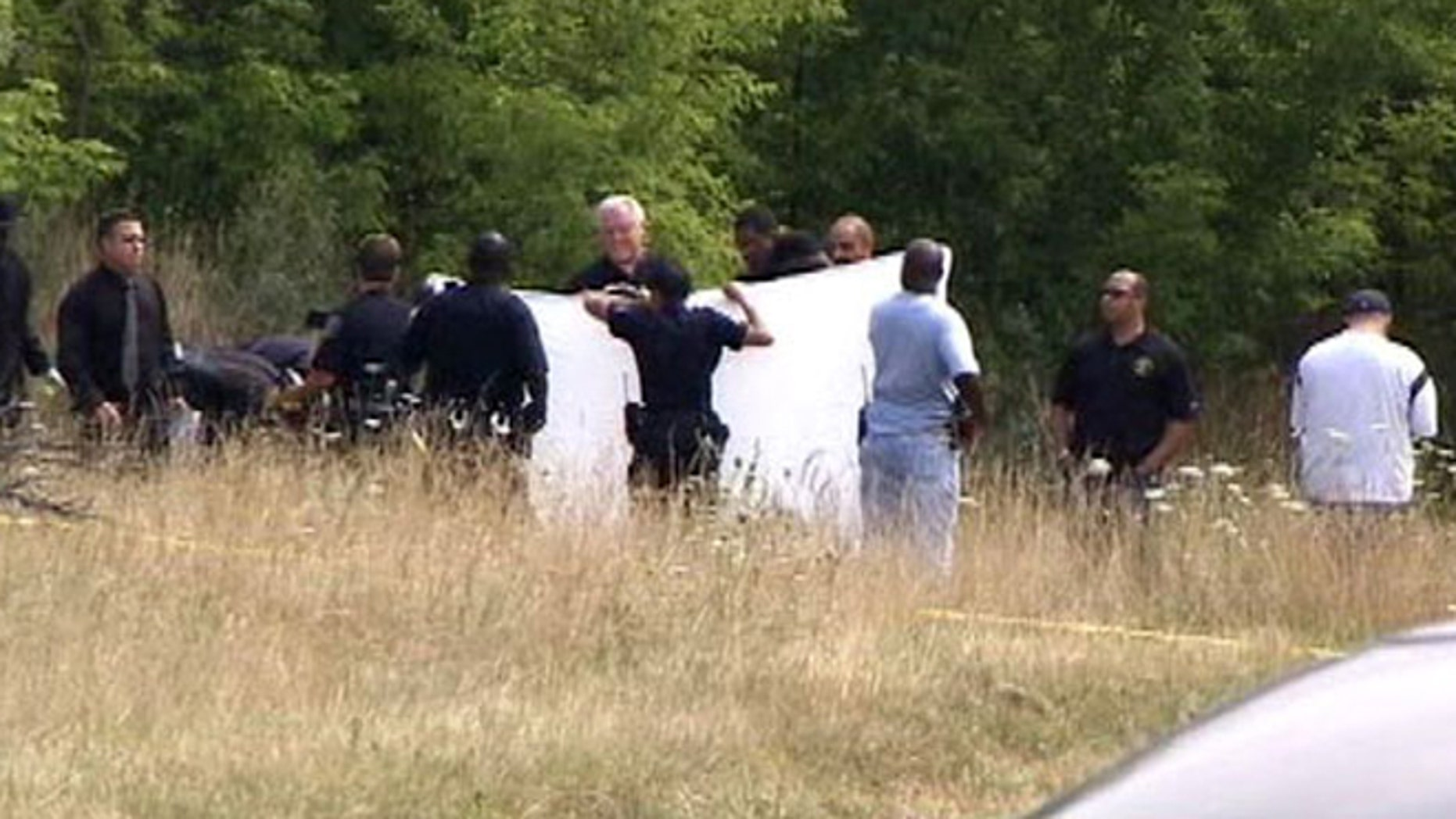 Detroit police block a road near where sources say two bodies were discovered Friday morning.