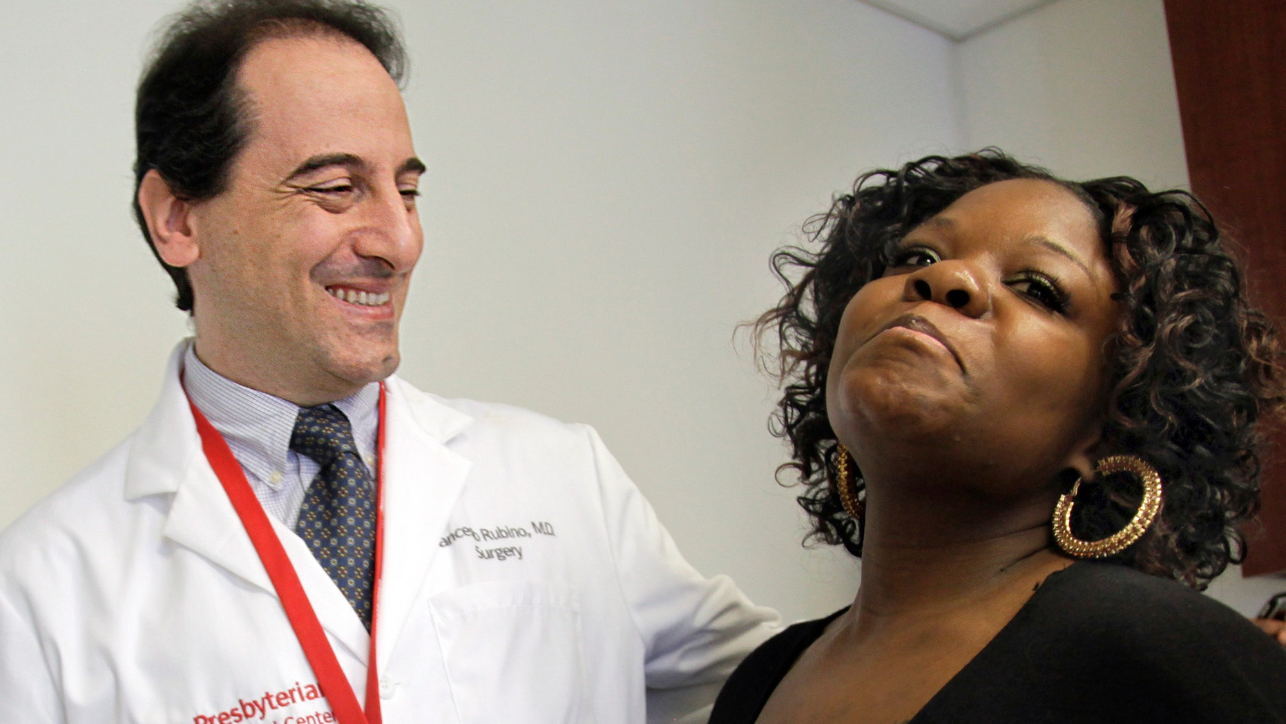 In this March 23, 2012 photo, Dr. Francesco Rubino, a surgeon at Weill Cornell Medical Center, joins his patient Tamikka McCray, 39, for an interview in New York. McCray no longer needed to take diabetes medication and insulin after her weigh-loss surgery. Research by Dr. Francesco Rubino, McCray's surgeon at Weill Cornell, and other doctors gives clear proof that weight-loss surgery can reverse and possibly cure diabetes. (AP Photo/Bebeto Matthews)