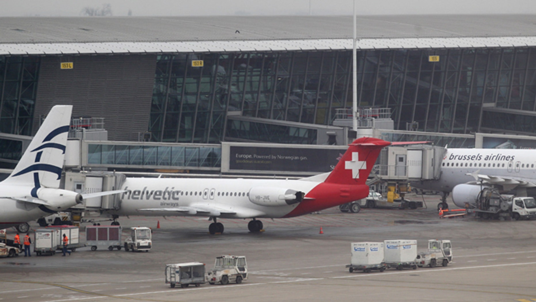 Feb. 19: Baggage carts make their way past a Helvetic Airways aircraft from which millions' of dollars worth of diamonds were stolen on the tarmac of Brussels international airport.