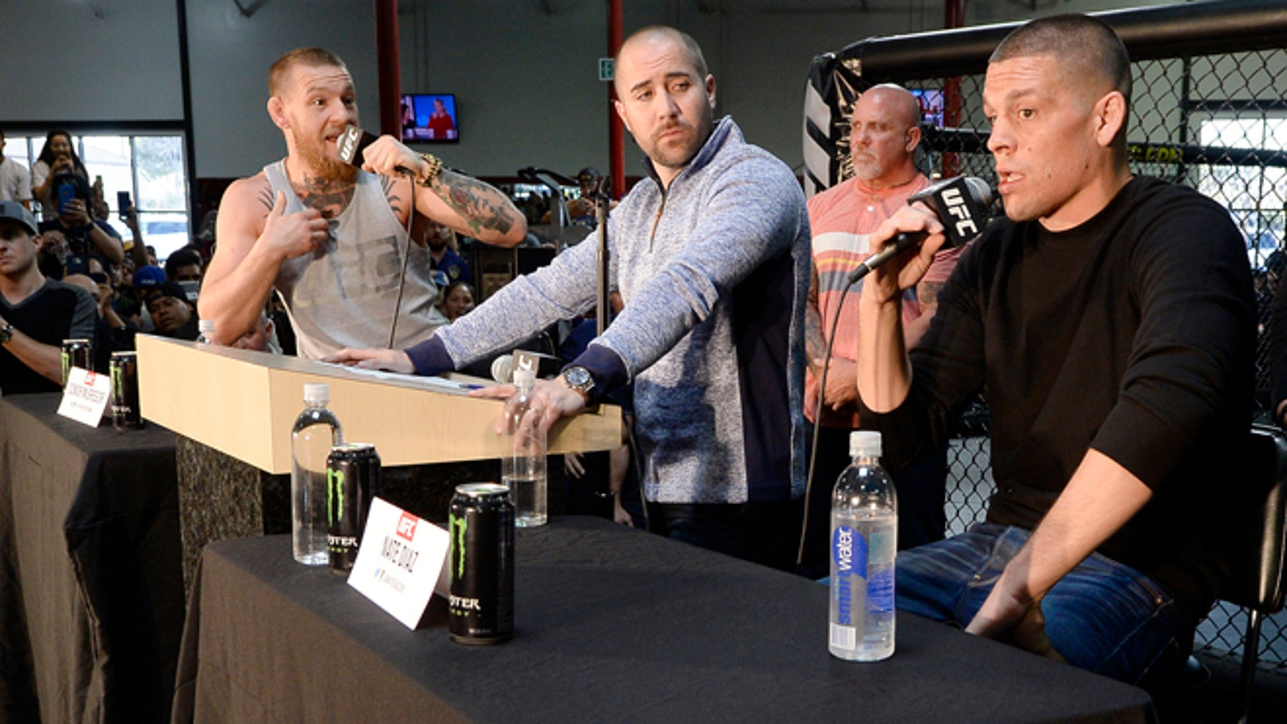 TORRANCE, CA - FEBRUARY 24: UFC featherweight champion Conor McGregor (L) and lightweight contender Nate Diaz (R) participate in a news conference with moderator Dave Sholler (C), UFC vice president of public relations, at UFC Gym February 24, 2016, in Torrance, California. (Photo by Kevork Djansezian/Getty Images)