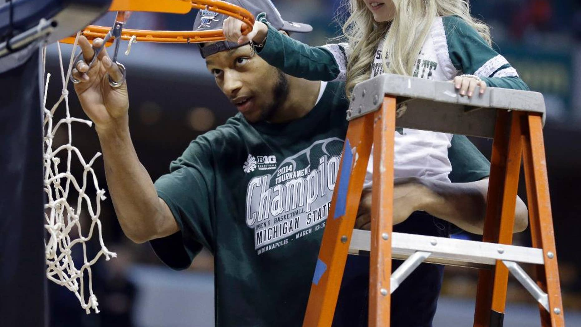 In this March 16, 2014, file photo, Michigan State forward Adreian Payne, left, cuts the net with Lacey Holsworth. Holsworth died in April 2014, after a battle with nerve-cell cancer.  (AP Photo/Michael Conroy, File)