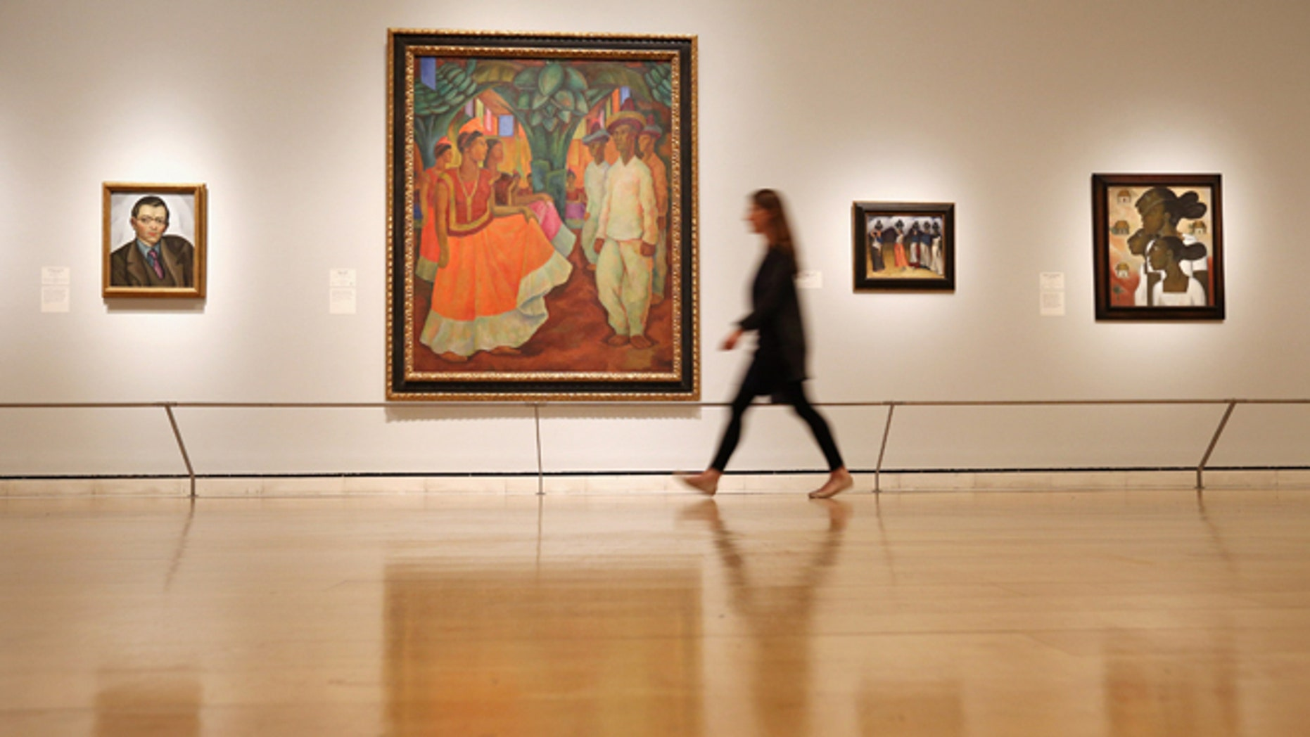 LONDON, ENGLAND - JULY 02:  A woman walks past a painting by Diego Rivera entitled 'Dance in Tehuantepec' (C) in the Royal Academy of Arts on July 2, 2013 in London, England. The painting features in the exhibition 'Mexico: A Revolution in Art, 1910-1940' which examines artworks influenced by the period of revolution and turmoil in Mexico between 1910 and 1920. The exhibition, which showcases 120 paintings and photographs, open to the public on July 6, 2013 and runs until September 29, 2013.  (Photo by Oli Scarff/Getty Images)