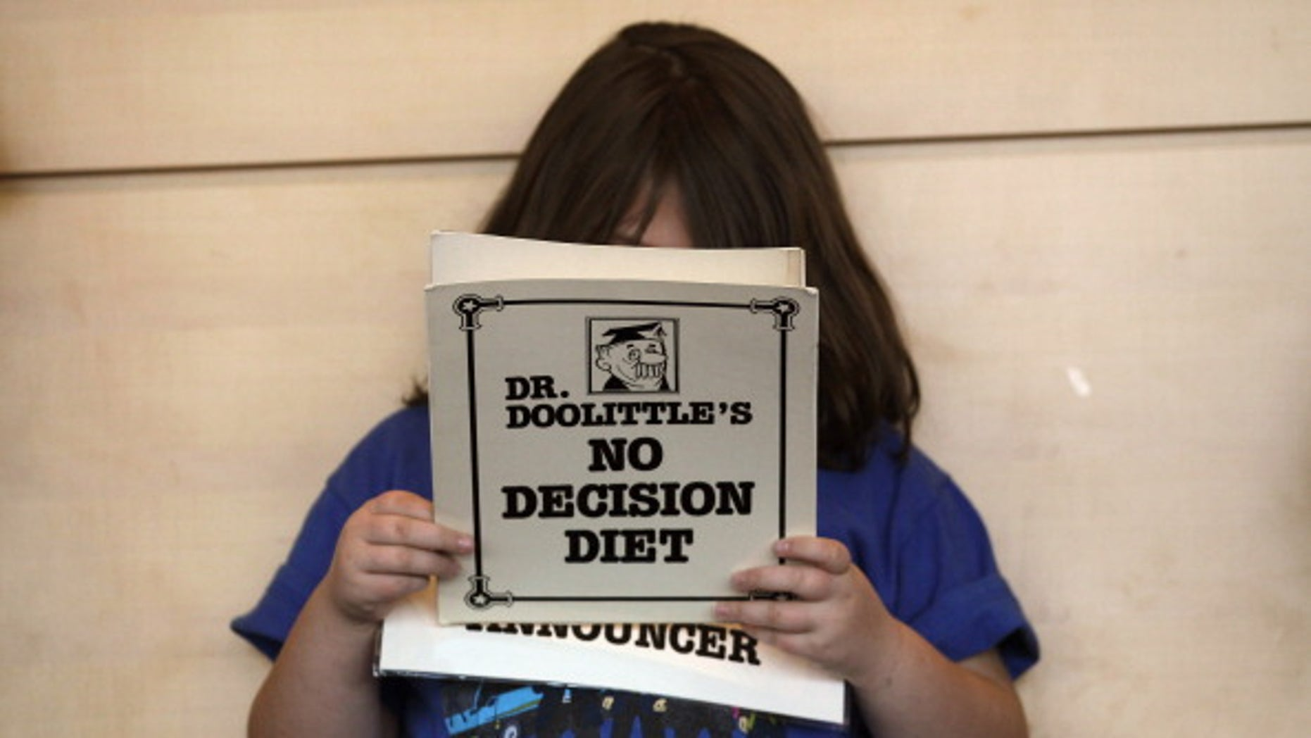 An overweight child reads her part in a humorous skit held during a program for overweight adolescents in Colorado.