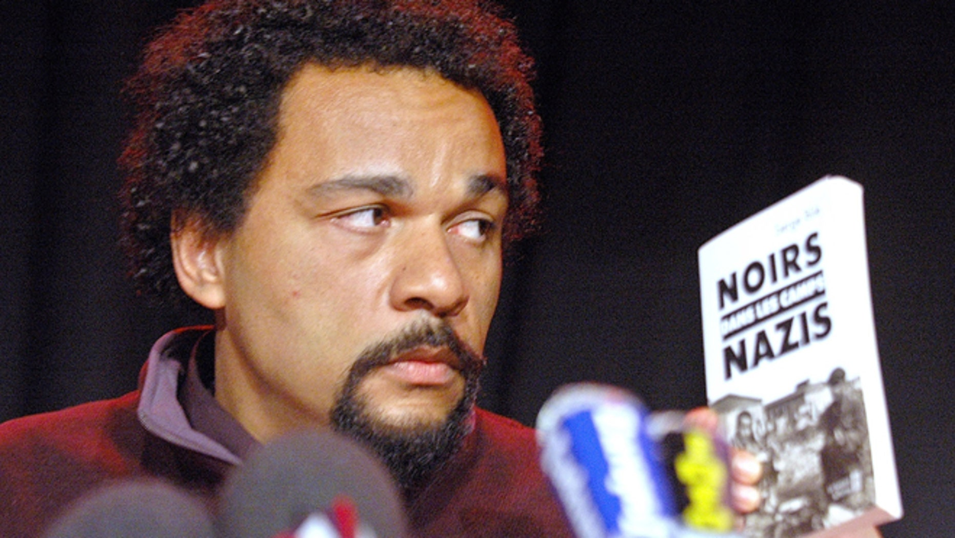 "Feb. 19, 2005: French comic Dieudonne M'Bala M'Bala looks at a book ""Blacks in the Nazi camps"" by Serge Bile during a statement at La Main d'Or theater, in Paris."