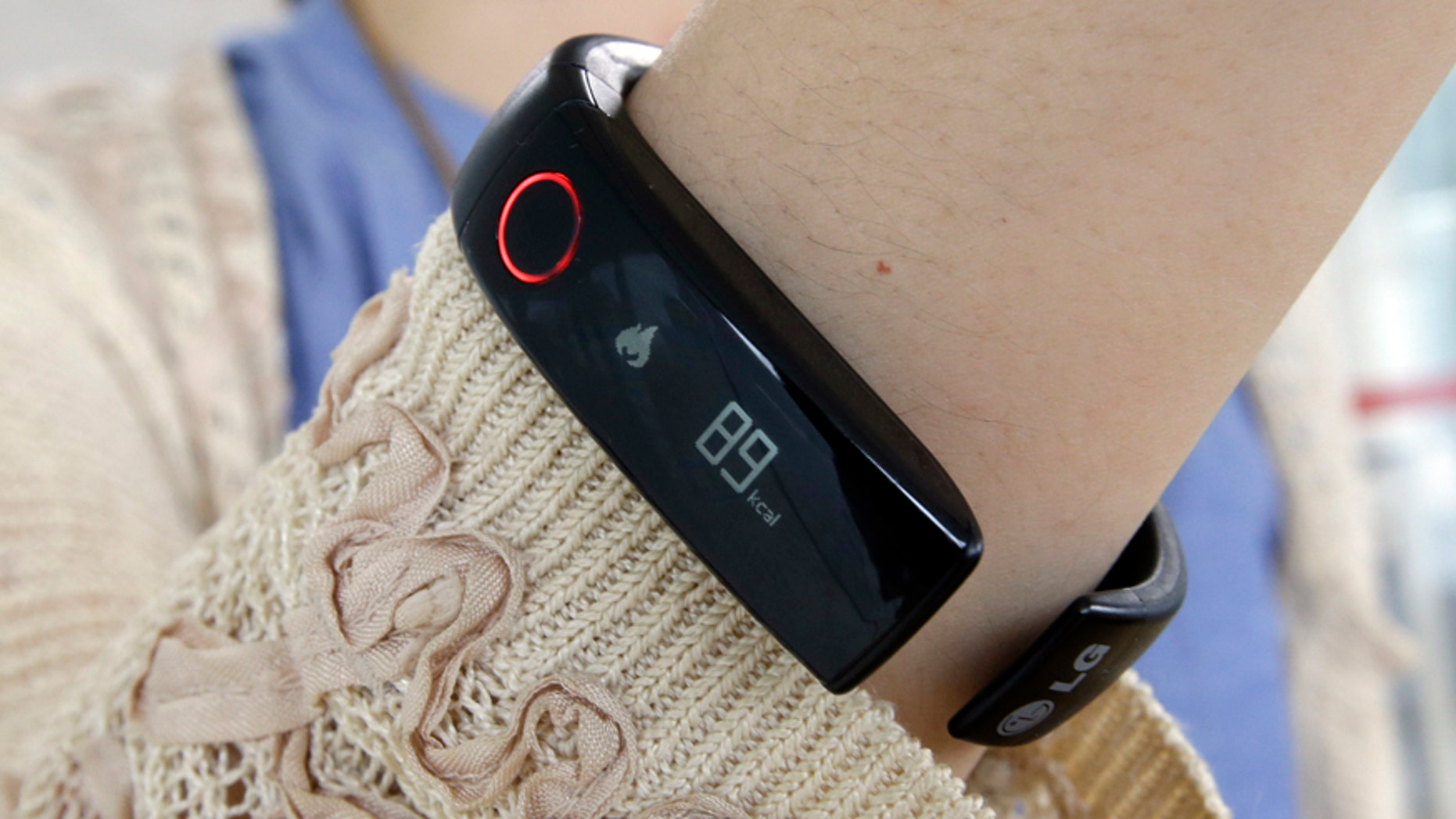 In this June 5, 2014 photo, a reporter shows LGs Lifeband Touch for photographs in Seoul, South Korea.