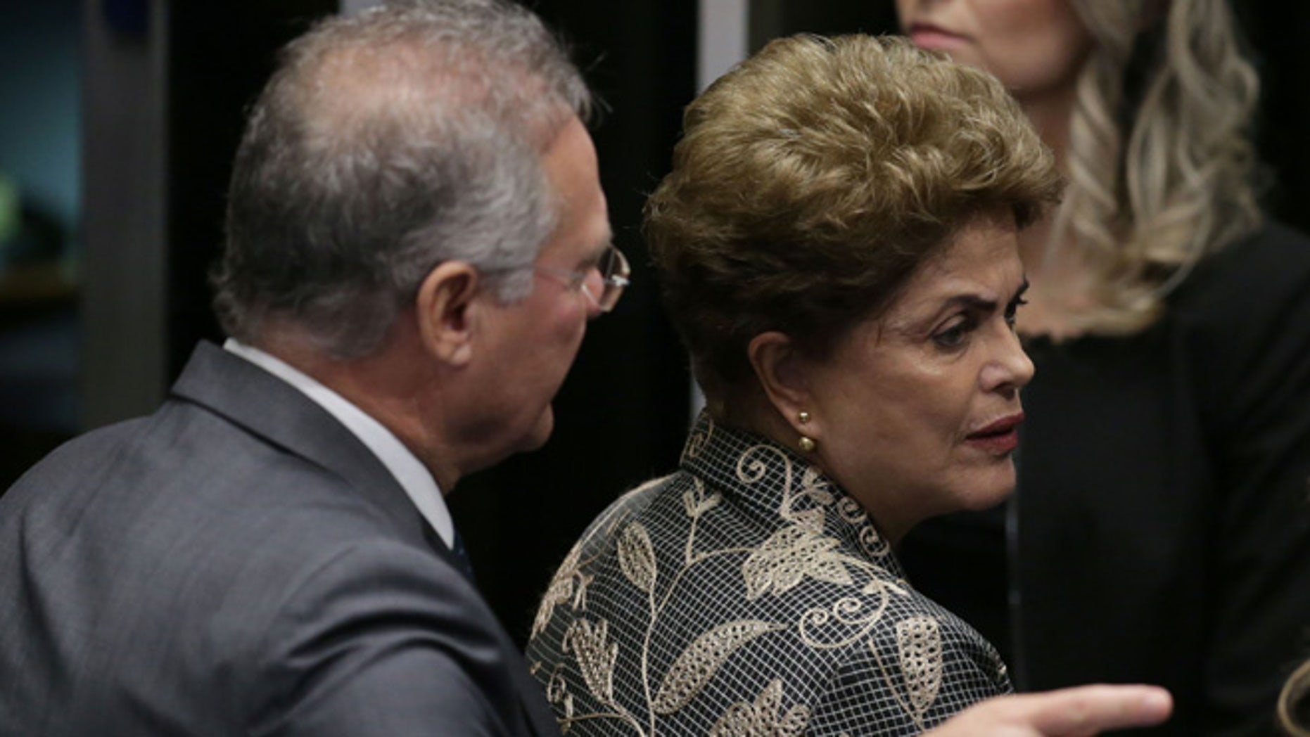 """Brazil's Senate leader Renan Calheiros points to an exit as suspended President Dilma Rousseff looks to leave Senate chambers after addressing the lawmakers, at the start of a short recess of her own impeachment trial, in Brasilia, Brazil, Monday, Aug. 29, 2016. Fighting to save her job, Rousseff told senators on Monday that the allegations against her have no merit. """"I know I will be judged, but my conscience is clear. I did not commit a crime,"""" she told senators. Rousseff's address comes on the fourth day of the trial. (AP Photo/Eraldo Peres)"""
