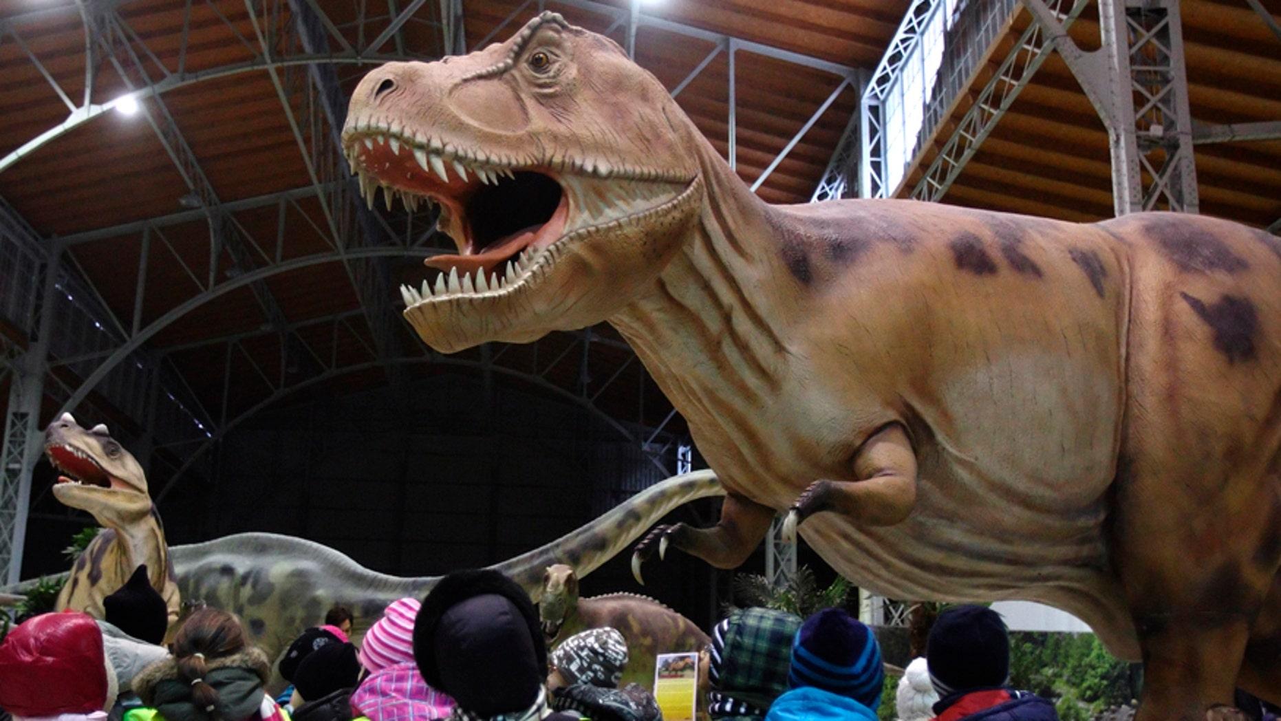 Children watch a life-sized Tyrannosaurus Rex dinosaur model in Vienna Feb. 7, 2014.