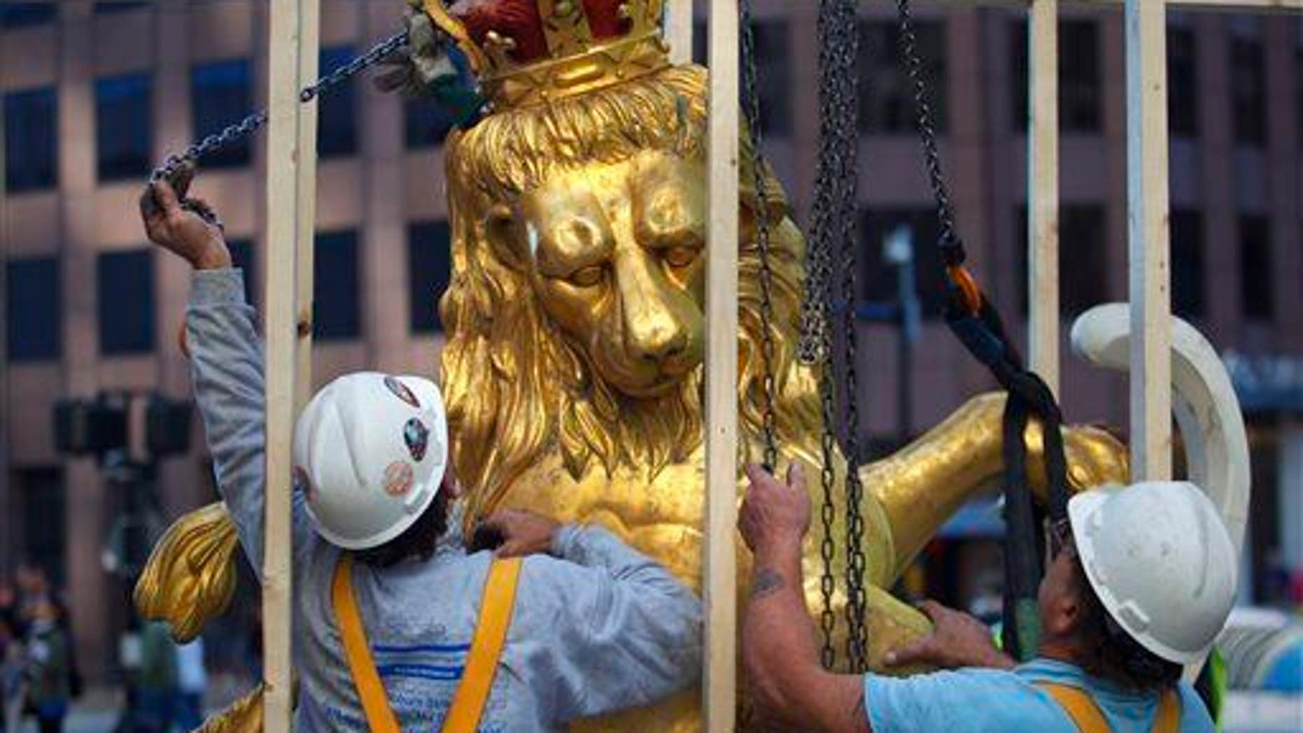 In this Sept. 14, 2014 file photo, a lion statue is removed from atop the Old State House on Washington Street in Boston.