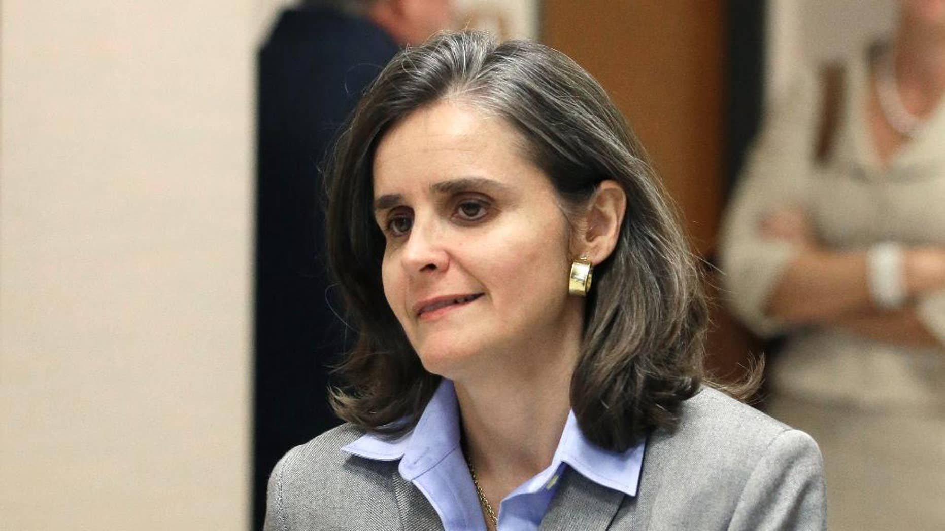 Dr. Ana Maria Gonzalez-Angulo takes a break from the courtroom during jury deliberations in her assault case Wednesday, Sept. 24, 2014, in Houston. The breast cancer doctor is accused of poisoning a fellow physician boyfriend with coffee laced with ethylene glycol. The case has gone to the jury, deliberations will continue Friday. (AP Photo/Pat Sullivan)
