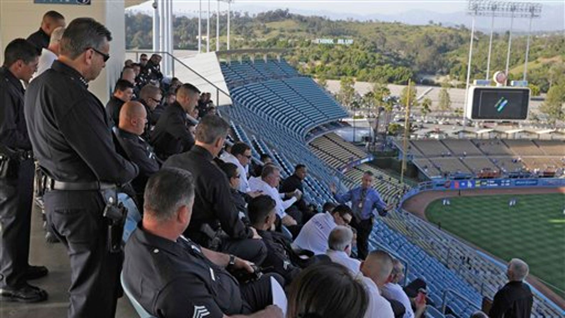 April 14: Los Angeles Police Department chief Charlie Beck, left, listens in on a meeting with police officer and security at Dodger Stadium prior to the Dodgers' Major League Baseball game against the St. Louis Cardinals in Los Angeles. Bryan Stow, the father of two, was beaten in a parking lot outside Dodger Stadium after the teams' March 31 season opener and remains hospitalized in Los Angeles in a medically induced coma. (AP)