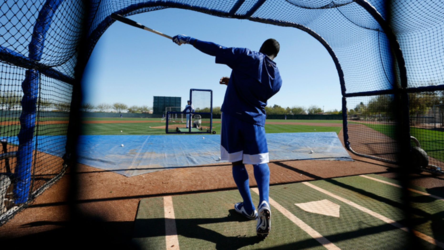 Los Angeles Dodgers' Yasiel Puig points out his shot after hitting a ball during a spring training baseball workout Wednesday, Feb. 25, 2015, in Phoenix. (AP Photo/John Locher)